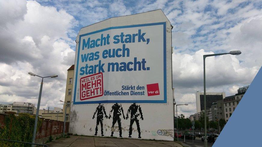Häuserwand Berlin mit ver.di-Slogan:Macht stark, was euch stark macht